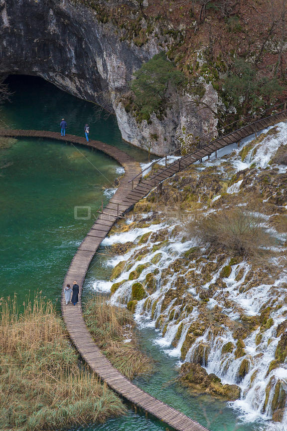 Tourists walking on boardwalk below Velike Kaskade waterfalls, Plitvice Lakes National Park, Croatia. January 2015.