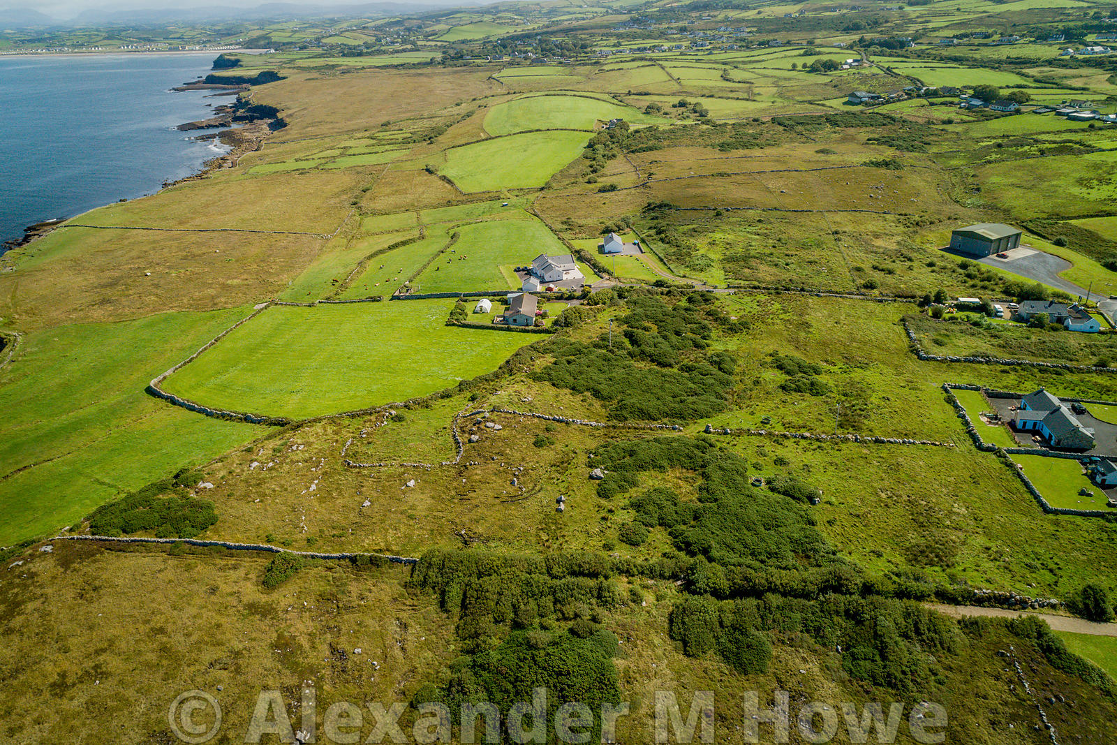Aerial view of farmland surrounding Creevy Pier, Co Donegal with the Mediterranean blue sea of Donegal Bay