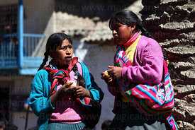 Girls holding oranges in street , Paucartambo , Cusco Region , Peru