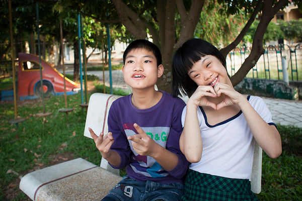 Deux amoureux sur un banc dans le parc du Village de l'amitié, Hanoi, Vietnam / Two lovers on a bench in the park of Friendsh...