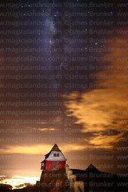 Milky Way and wind blown cloud above old ski hut on Mt Chacaltaya at night, lights of El Alto city in background, Bolivia