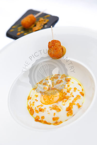 Poached egg yolk, smoked haddock milk foam, cornflakes, curry oil