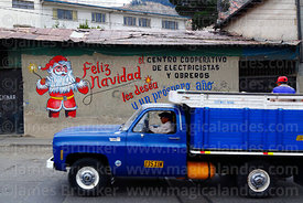 Vintage blue truck driving past Father Christmas mural on wall of the offices of an electricians and electrical workers coope...