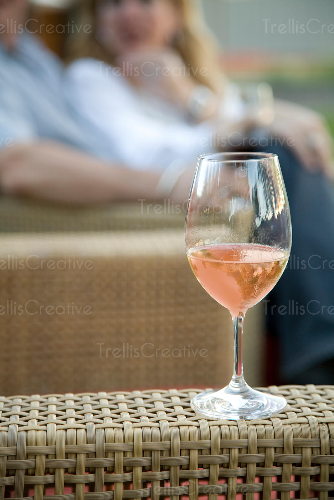 glass of rose wine on rattan chair with couple in background