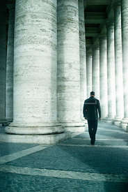 An atmospheric image of a mystery man, walking away, through the columns at Saint Peter's Square, Rome, Italy.