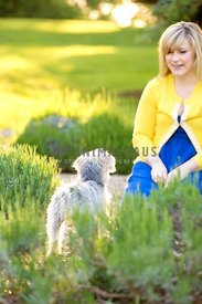 woman smiling at small dog in lavender