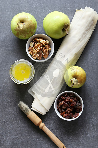 Ingredients for making apple strudel.Apple,raisins,walnuts,filo pastry and butter