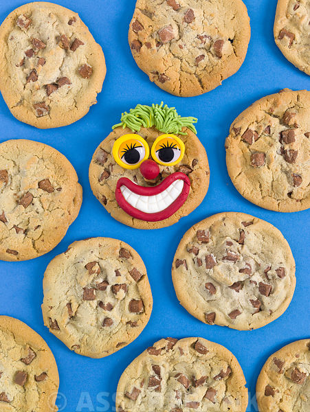 Face shaped biscuits amongst cookies on blue background