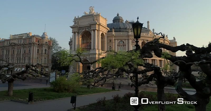 Aerial camera tracks slowly pass pretty trees with Odessa Opera House Ukraine