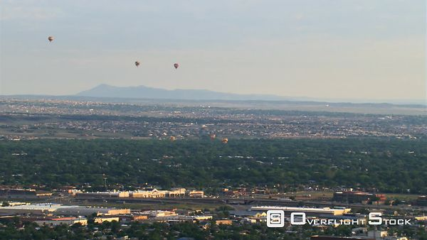 Wide orbit of downtown Albuquerque with hot air balloons floating above.