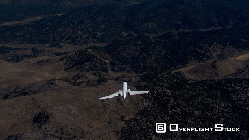 Air-to-air view of small jet over rugged terrain