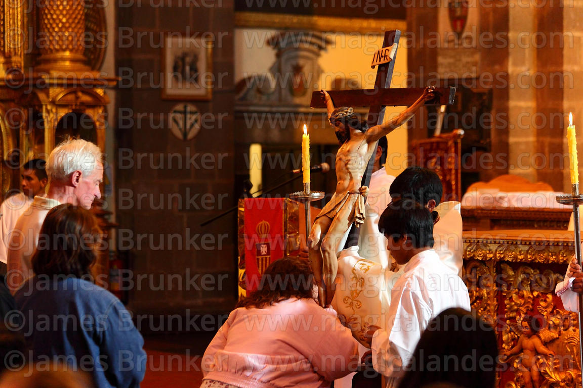 Devotee kisses feet of crucified Christ during Good Friday mass in La Merced church , Cusco , Peru