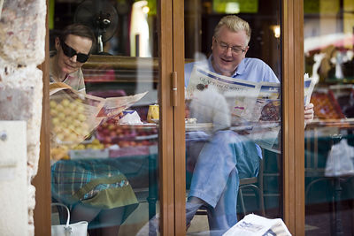 France - Paris - A couple read newspapers in the window of a cafe on the Rue Mouffetard.