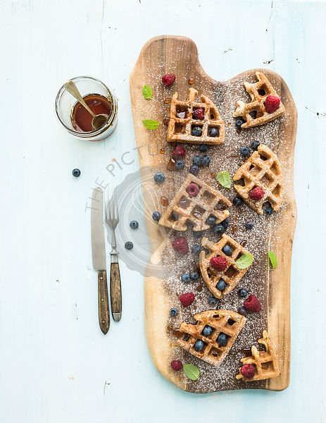 Soft Belgian waffles with berries, honey and mint on rustic wooden serving board over light blue background, top view