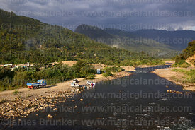 People washing vehicles in river near Caranavi, Bolivia