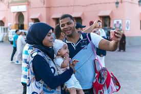 Tourists taking selfies at the square Jemaa-el Fnaa in Marrakesh, Morocco