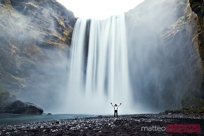 Young tourist in front of Skogafoss waterfall, Iceland
