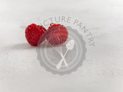 Close detail shot of two fresh raspberries on white textured surface.