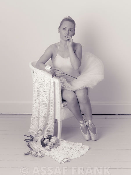 Pretty young ballet dancer sitting on a chair with a Rose