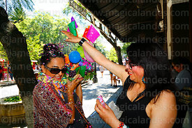 A woman greets her friend / comadre and sprinkles confetti over her during the Comadres festival, Tarija, Bolivia