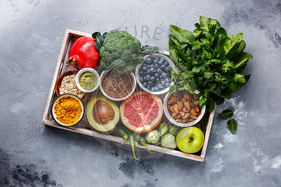 Healthy food clean eating selection in wooden box: fruit, vegetable, seeds, superfood, cereals, leaf vegetable on gray concre...