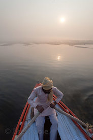 A boatman at sunrise on the Ganges River, Varanasi, India.