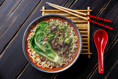 Miso Ramen Asian noodles with beef and pak choi cabbage on dark wooden background