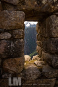 View of mountains through opening in stone wall at Machu Picchu.