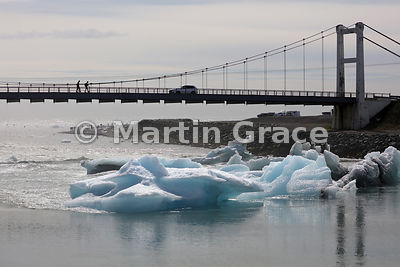 Suspension bridge over River Jokulsa, with icebergs, Jokulsarlon glacier lagoon, Austurland (Eastern Region, East Iceland), I...