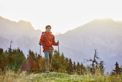 Austria, Tyrol, Mieming Plateau, portrait of hiker on alpine meadow at sunrise