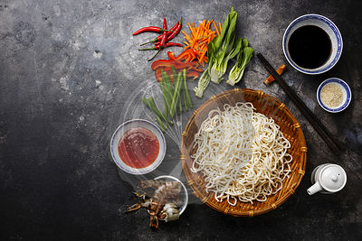 Raw Udon noodles in bamboo basket and Ingredients for cooking asian food with Tiger shrimps, greens, vegetables, spices on da...