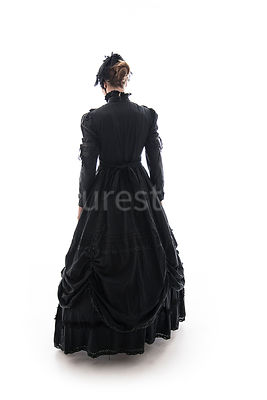 A Victorian woman, in a dress and hat, walking away – shot from eye level.