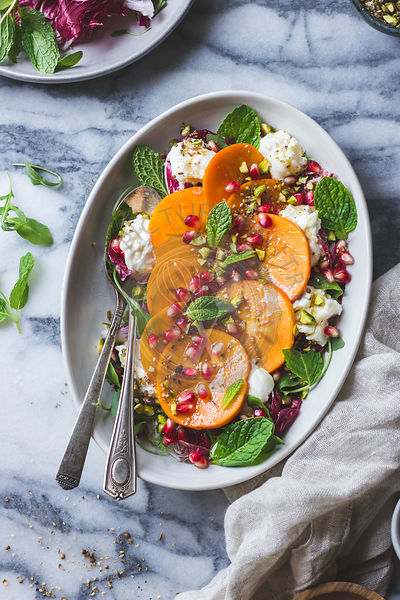 Persimmon pomegranate salad on marble