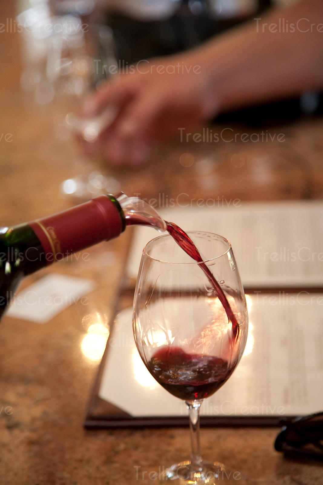 Server pouring red wine into wine glass in tasting room