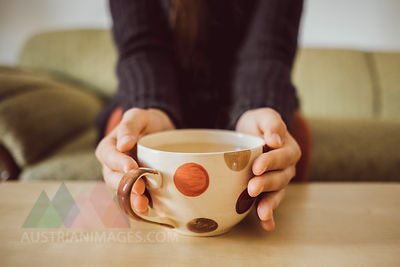 Woman's hands holding tea cup, close-up