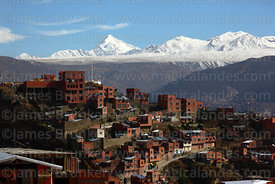 Houses on hillside below J'acha Kollo viewpoint and Mt Huayna Potosí after fresh winter snowfall, La Paz, Bolivia