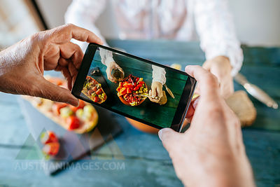 Close-up of man's hands taking a picture with mobile phone eating salad of tomato, pomegranate, papaya and olives, with papaya with fruits on the side and with glass of wine