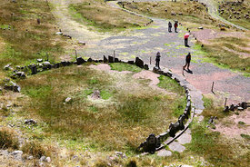Tourists and stone circle with intihuatana, probably from Inca period, Sillustani, Peru