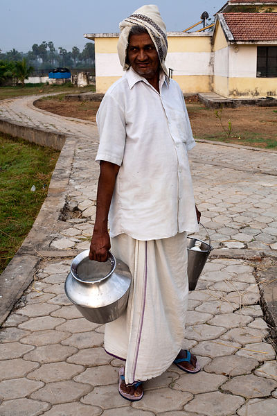 India - Cuddalore - Natrajan walks back from milking the cows in the dairy with a pail of milk