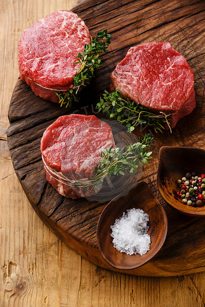 Raw fresh marbled meat Steak filet mignon and seasonings on wooden background