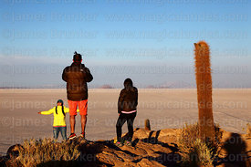 Tourists and Echinopsis atacamensis (pasacana subspecies) cactus on summit of Incahuasi Island shortly after sunrise, Salar d...