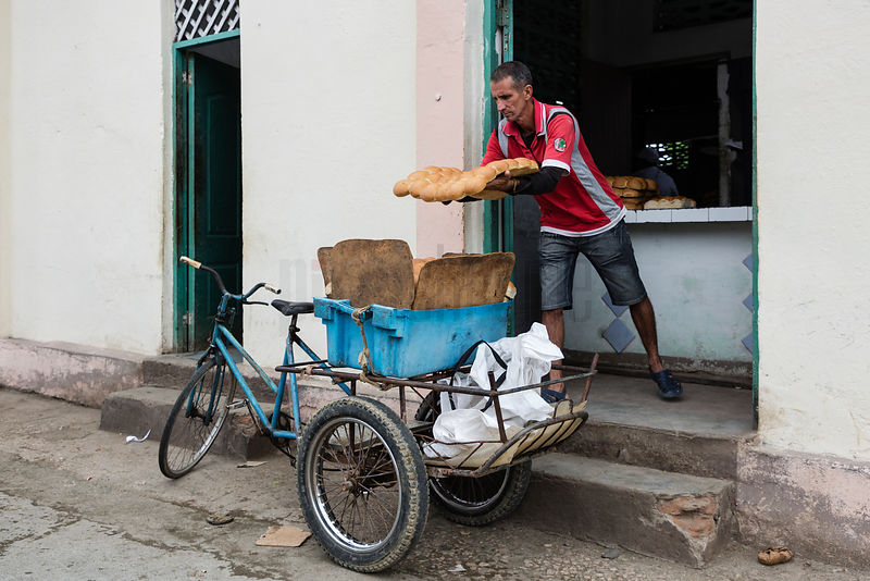 Man Loading Bread on to a Cart