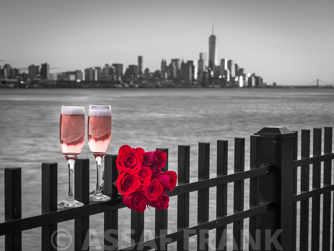 Glasses of Champagne with bunch of roses on railing against Lower Manhattan skylne, New York