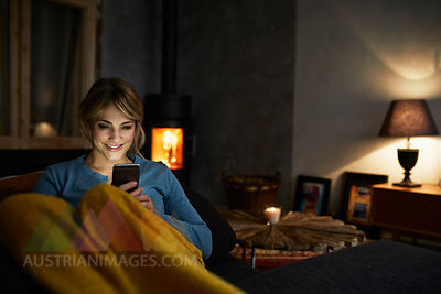 Portrait of smiling woman with smartphone relaxing on couch in the evening