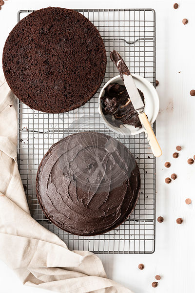 Gluten-free chocolate cake covered with chocolate icing and cut in halves.
