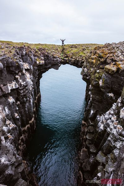 Man on top of natural rocky arch, Snaefellsnes peninsula, Iceland
