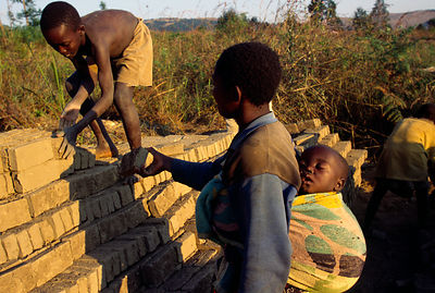 Burundi - Ruyigi - A child and his mother, pile bricks
