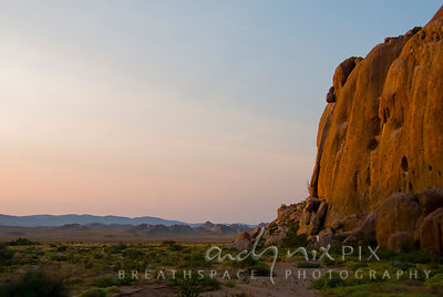 Early sunlight on orange granite cliffs on the edge of a flat desert plain, mountains in the distance