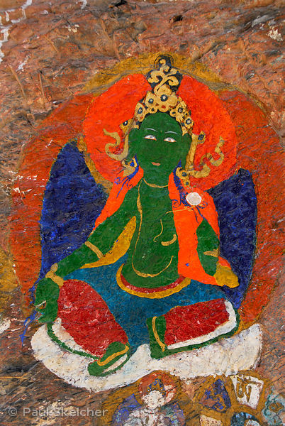 Painted rock carving on the Lingkhor pilgrim circuit as it ascends Chagpo Ri mountain, depicts Green Tara, or Drolma, female ...