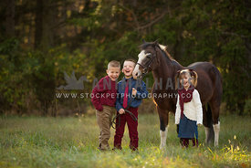 children laughing holding pony